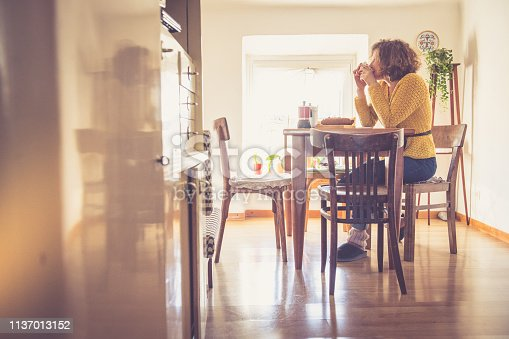 Young woman having breakfast in her kitchen. Italy.