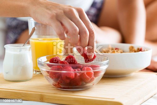 Close-up of young woman having breakfast in the bedroom.