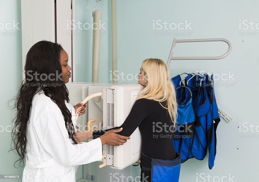 Young woman having chest x-ray,black radiologist is helping her royalty-free stock photo