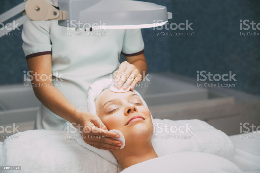 Young woman having cleaning facial treatment stock photo