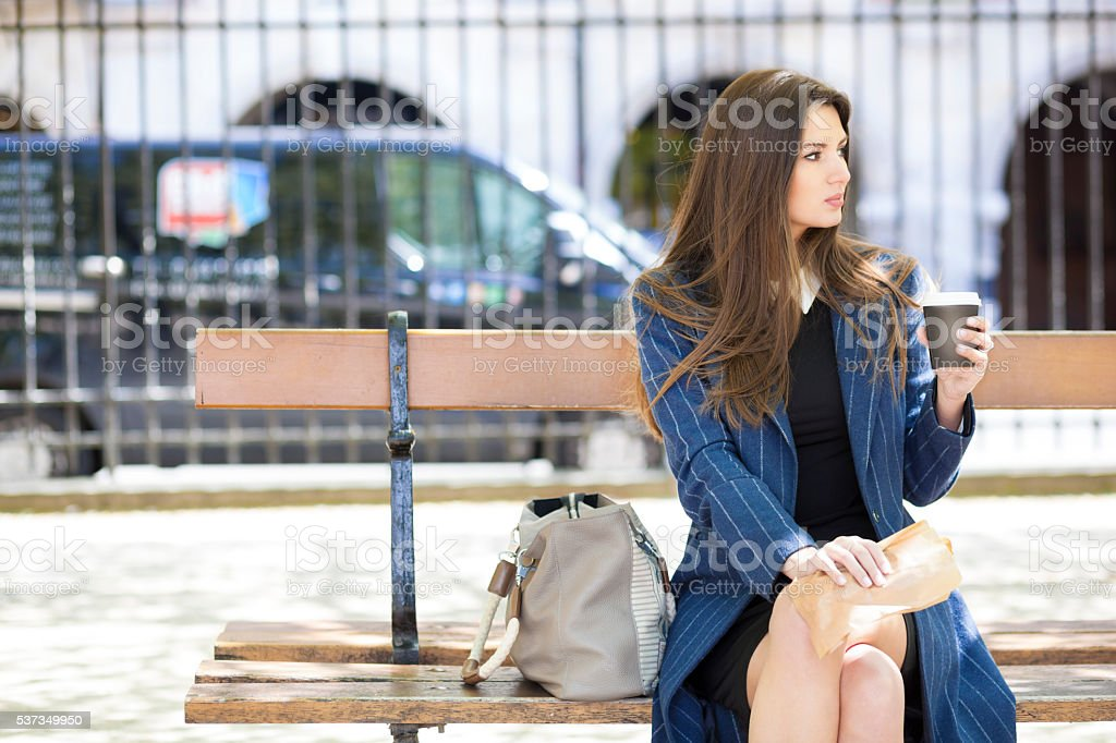 Young Woman Having Coffee and Snacks Sitting On A Bench stock photo