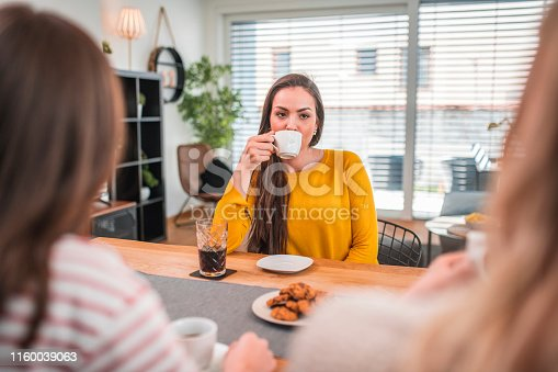 Young woman having coffee while looking at friend. They are socializing at home.