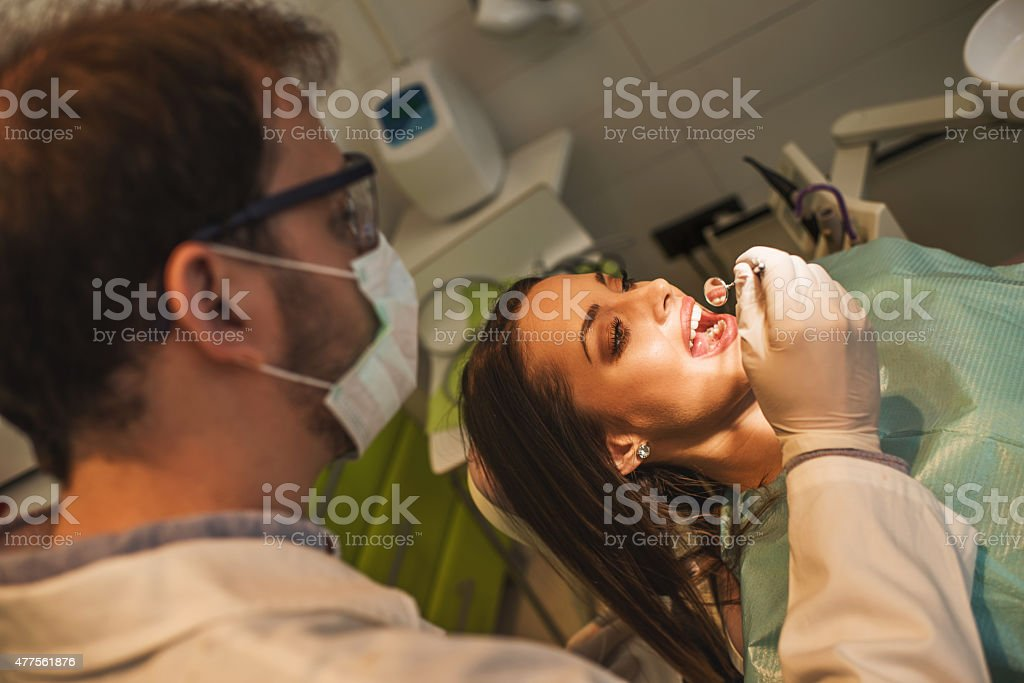 Young woman having dental examination at male dentist. stock photo