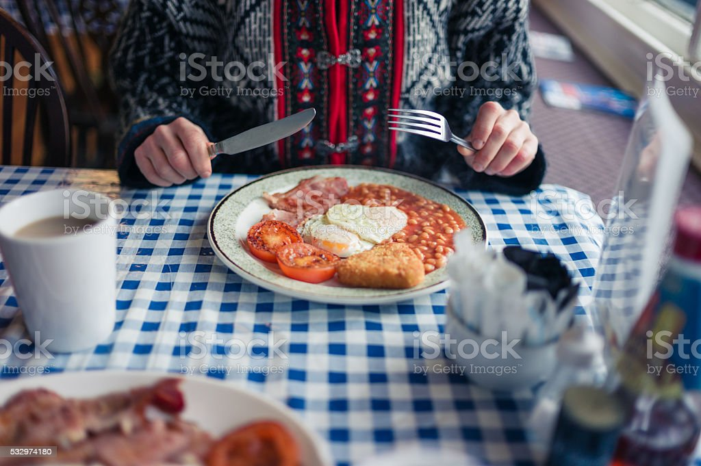 Young woman having english breakfast stock photo