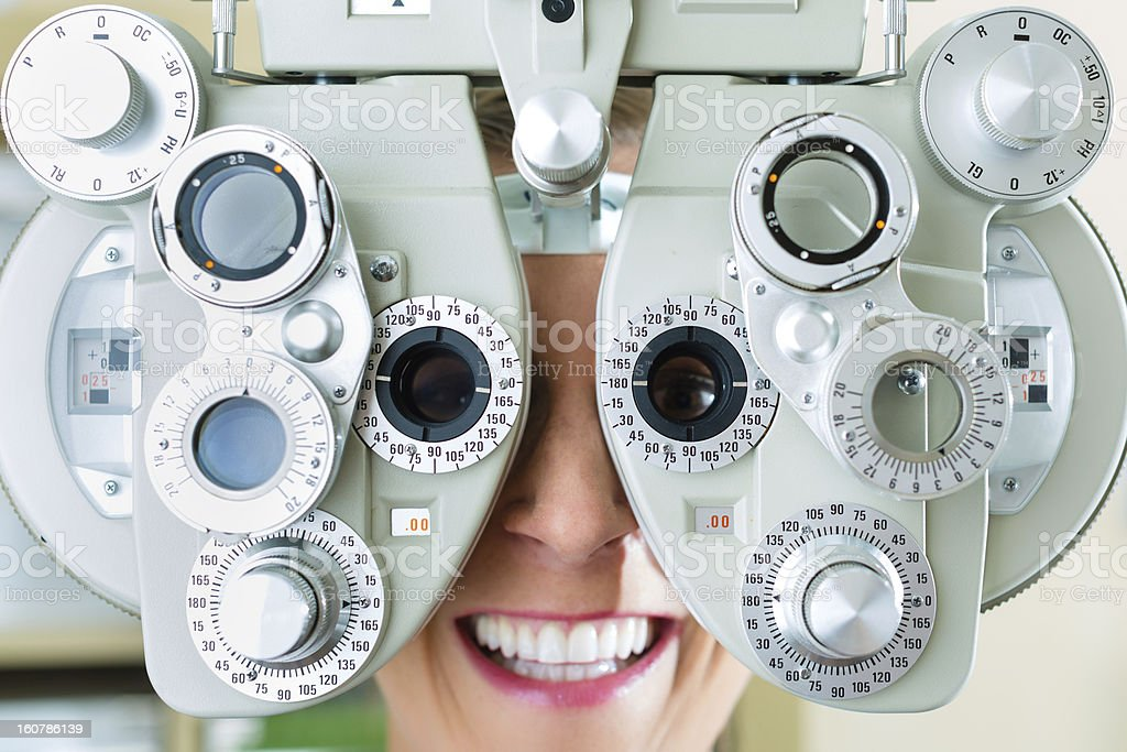 Young woman having eye test done with phoropter device stock photo