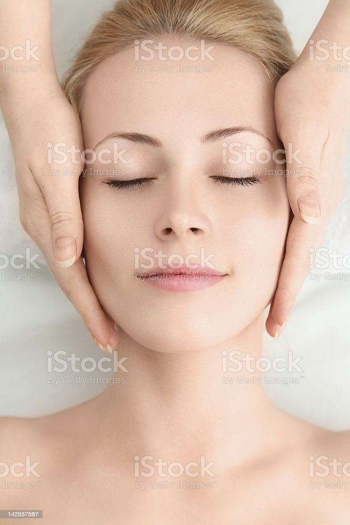 Young woman having face massage stock photo