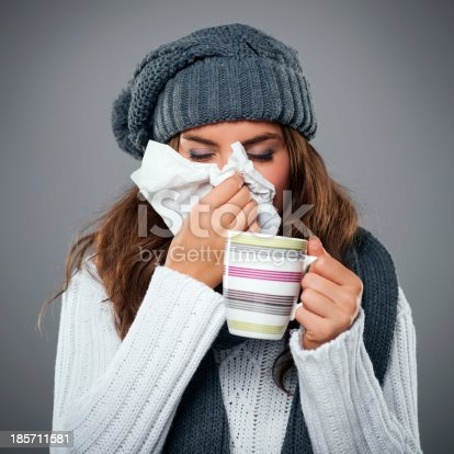 istock Young woman having flu and blowing her nose at handkerchief 185711581