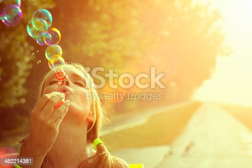 istock Young woman having fun and blowing bubbles outdoors 452214381