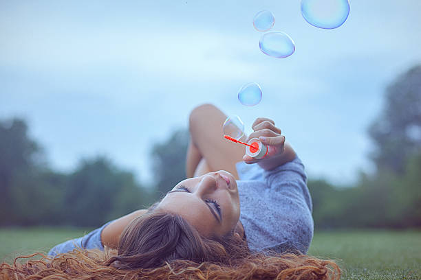 Young woman having fun and blowing bubbles outdoors stock photo