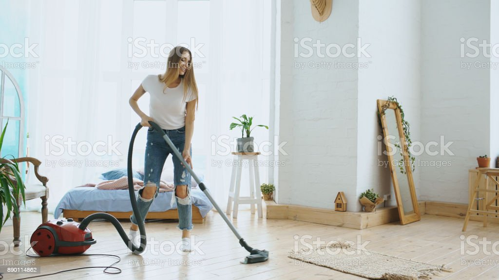 Young woman having fun cleaning house with vacuum cleaner dancing and singing at home stock photo