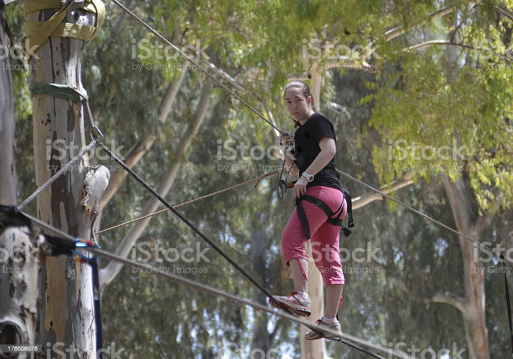 Young woman having fun on a rope park adventure course royalty-free stock photo