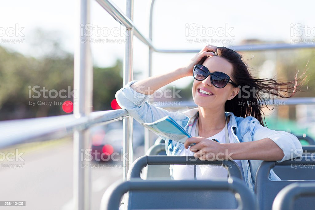 young woman having fun on an open top bus stock photo