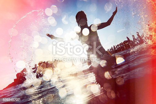 Silhouette of young woman splashing the water. Lomo Photo effect.