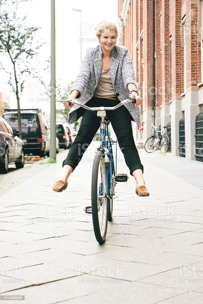 Trendy young woman having fun with her bike in city streets.