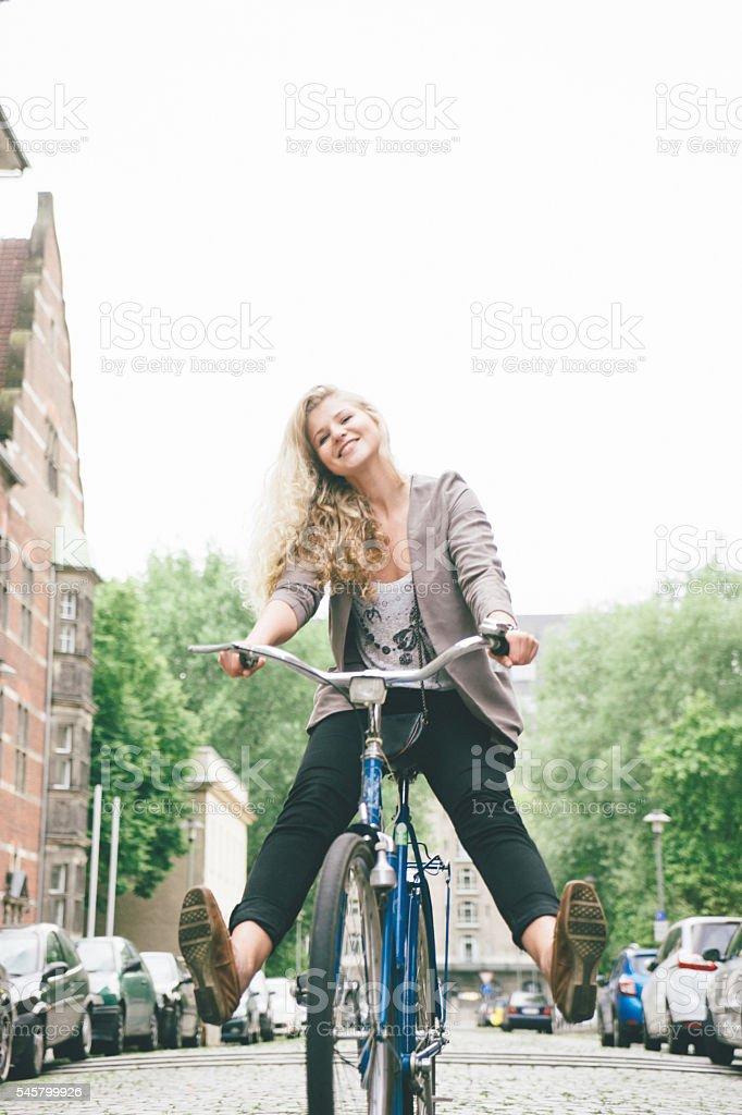 Jovem se divertindo andar de bicicleta nas ruas da cidade - foto de acervo