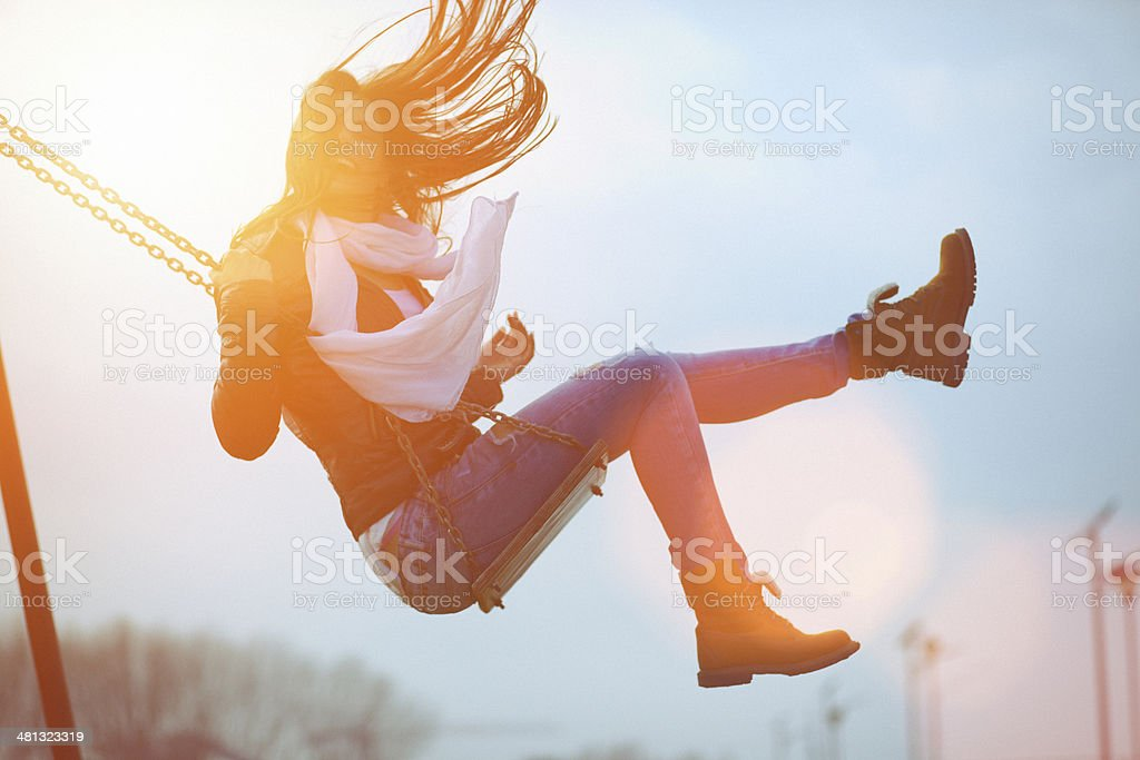 Young woman having fun swinging in sunlight royalty-free stock photo
