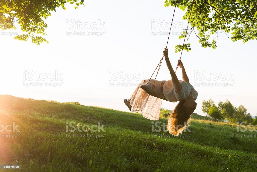 Young woman having fun swinging in sunlight stock photo