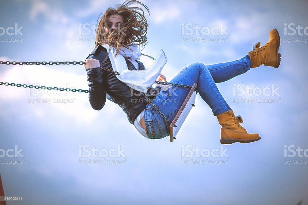 Young woman having fun swinging on a spring sunny day stock photo
