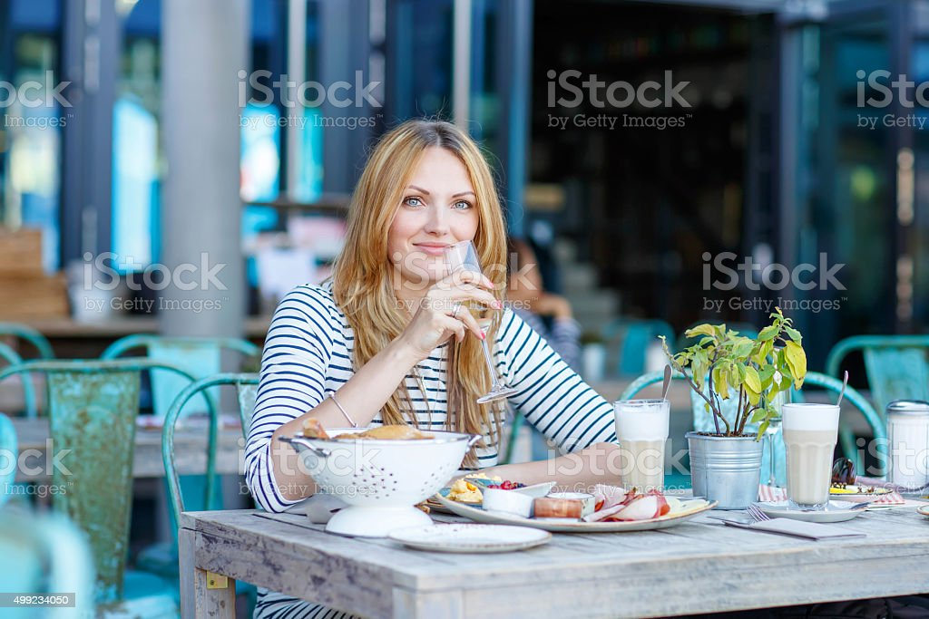 Young woman having healthy breakfast in outdoor cafe stock photo