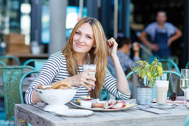 junge frau mit gesunden frühstück im café im außenbereich - genießen französisch stock-fotos und bilder