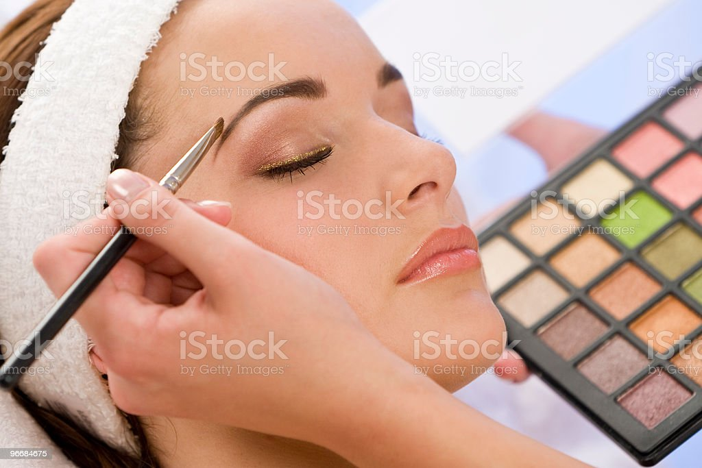 A young woman having make up applied royalty-free stock photo
