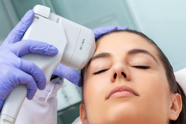 Young woman having non invasive ultrasound plasma lift treatment on face. stock photo
