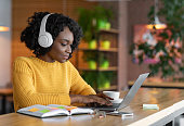 istock Young woman having online training, using laptop and wireless headset 1209016407