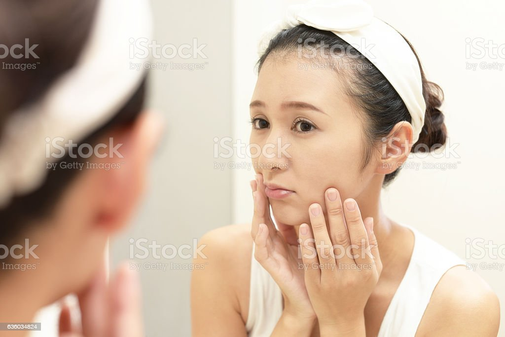 Young woman having skin problems stock photo