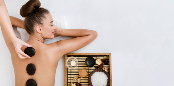 Young woman having stone massage in spa salon Young woman having stone massage in spa salon, top view, copy space spa stock pictures, royalty-free photos & images