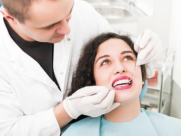 Young woman having teeth examined at dental office stock photo