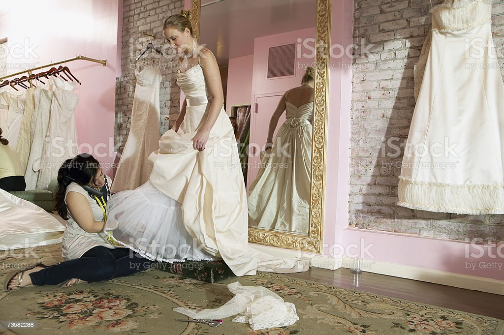 Young woman having wedding dress fitted royalty-free stock photo