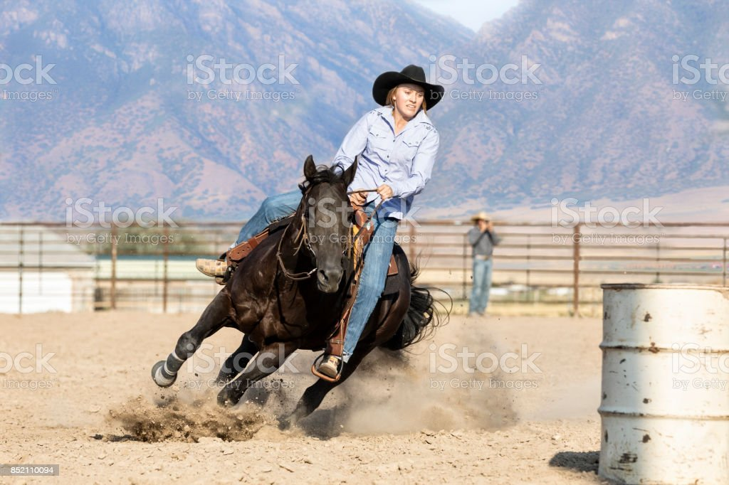 Young Woman heads her horse around a barrel during a barrel racing contest while her husband takes pictures in the background stock photo