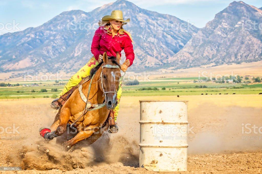 Jeune femme dirige son cheval autour d'un baril pendant un concours de course de baril - Photo