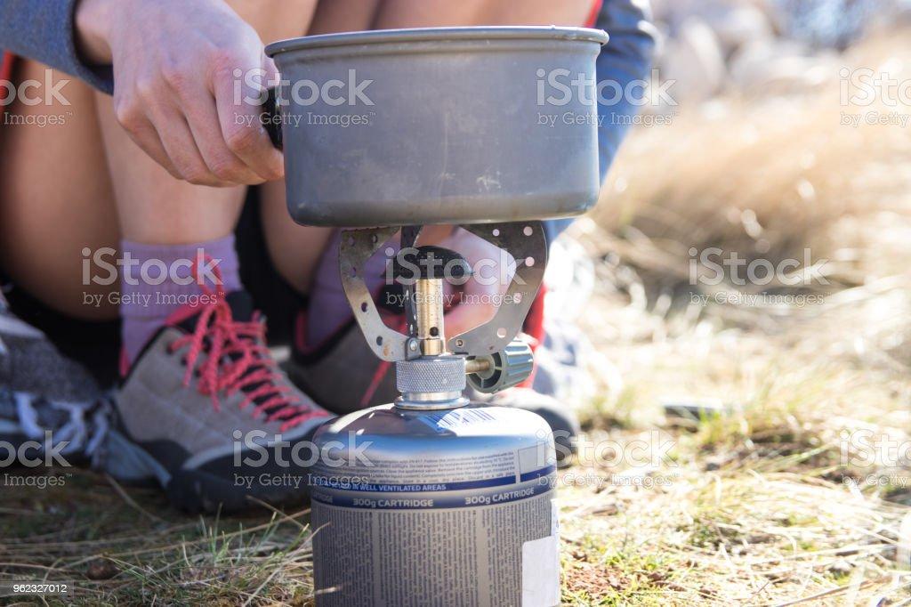 Junge Frau Die Warmwasserbereitung Mit Gas Herd Beim Camping Stock