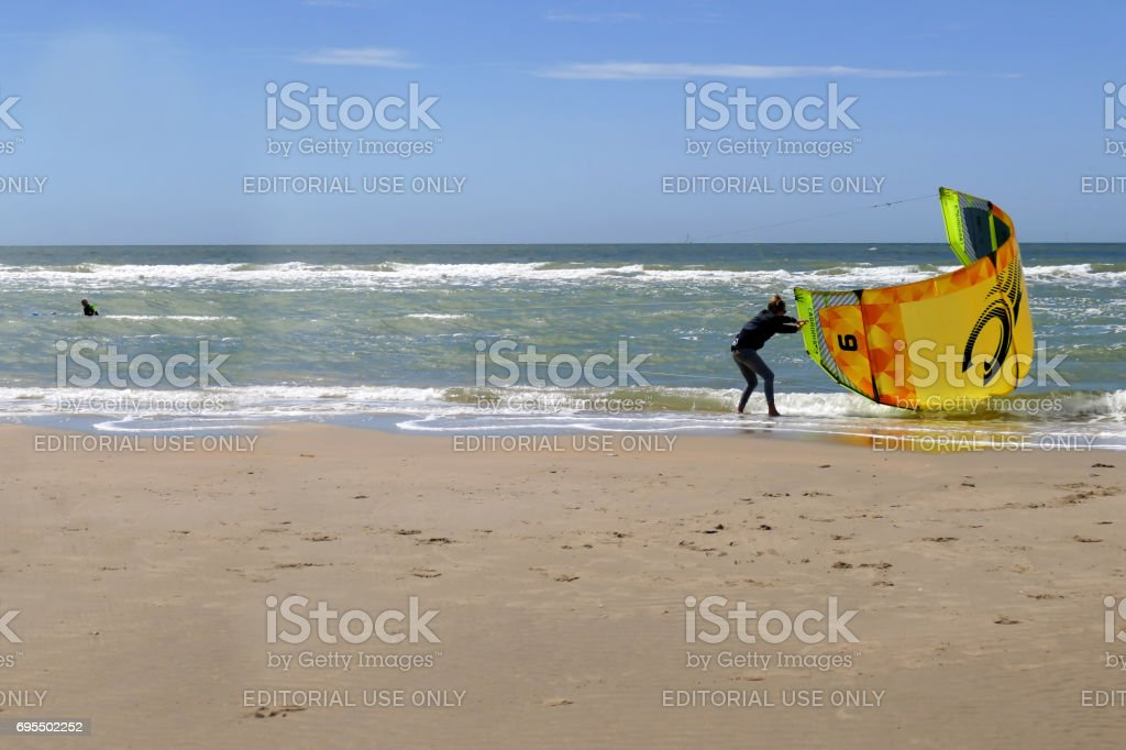 Young woman helping another woman handling her kite while getting out of the water stock photo