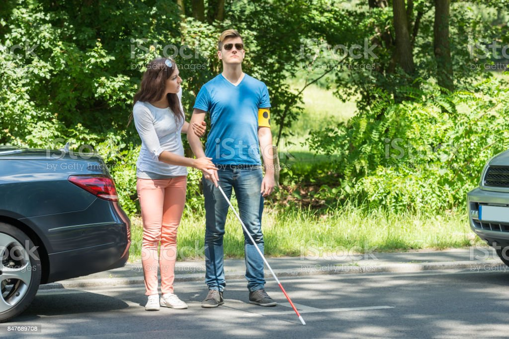 Young Woman Helping Blind Man stock photo