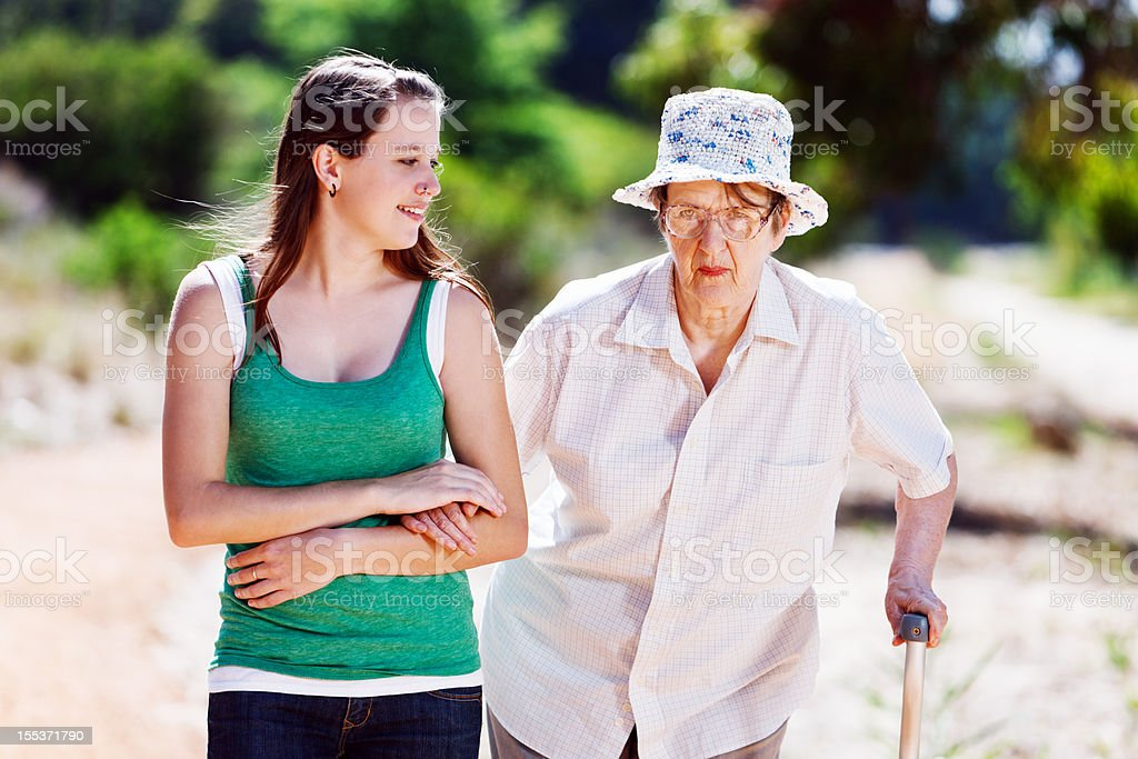 Young woman helping old lady with stick to walk stock photo