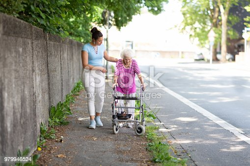 istock Young woman helping senior woman walking in the street 979946524