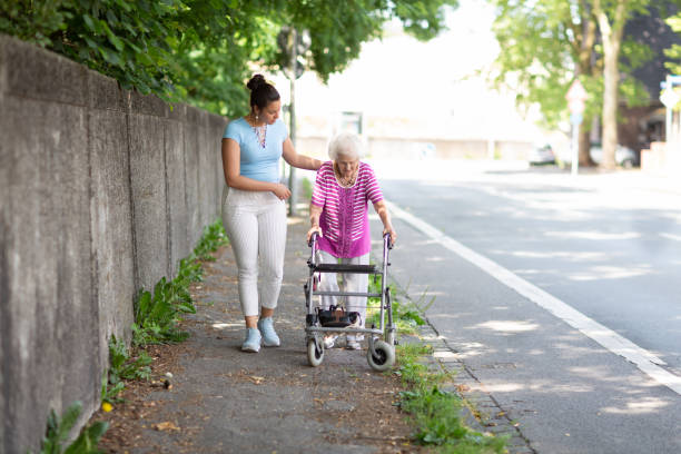 Young woman helping senior woman walking in the street stock photo