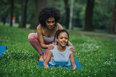 istock Young woman helping teenage girl stretch her bacjk 1023557382