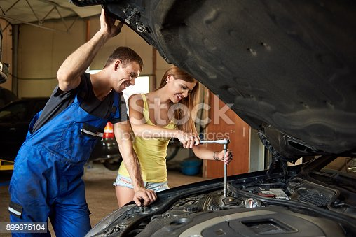 962888586 istock photo Young woman helps an auto mechanic repair a car in a garage. The girl unscrews the front right-hand stand. The guy holds the hood cover by hand 899675104
