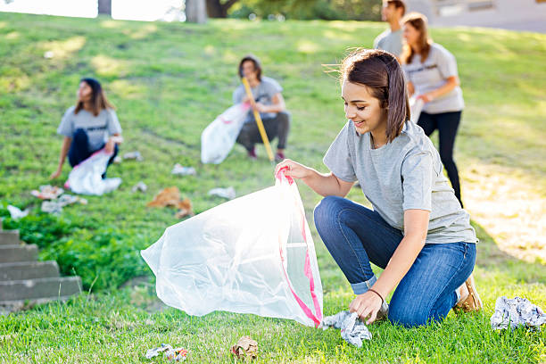 Young woman helps with community clean up Cheerful young Hispanic woman kneels down to pick up a wad of paper. She is holding a garbage bag. Her neighbors are in the background picking up trash. She is wearing blue jeans and a gray volunteer t-shirt. environmental cleanup stock pictures, royalty-free photos & images