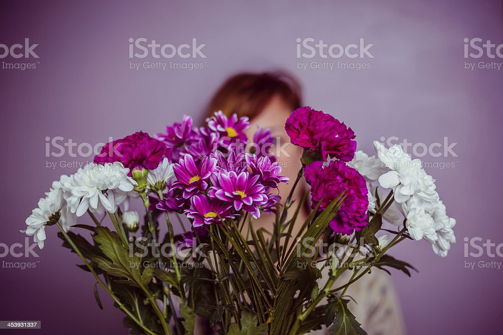 Young woman hiding behind a bouquet of flowers royalty-free stock photo