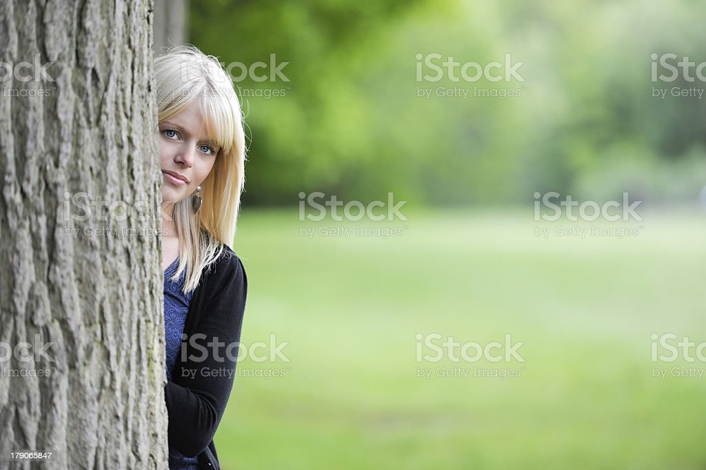 young woman hiding behind a tree royalty-free stock photo