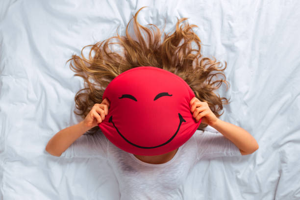 young woman hiding behind red pillow with smiley face print - excited emoji stock photos and pictures
