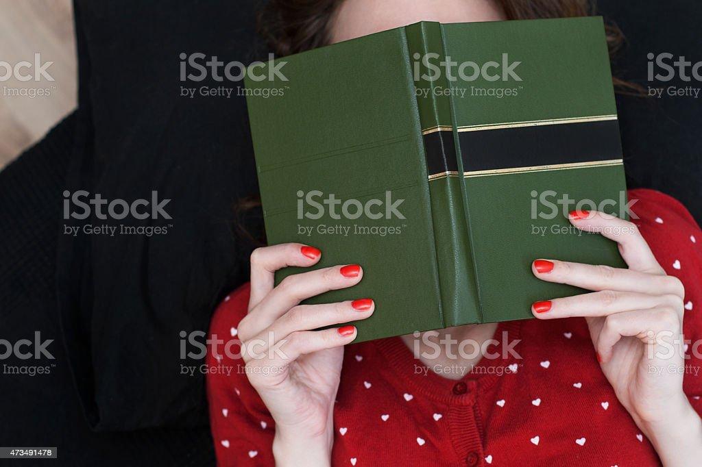 Young woman hiding face under a book foto