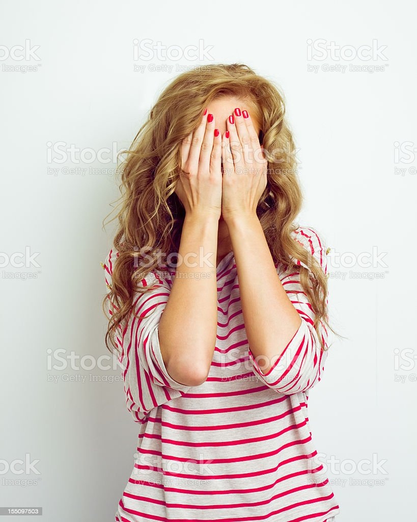 Young woman hiding her face with her hands stock photo