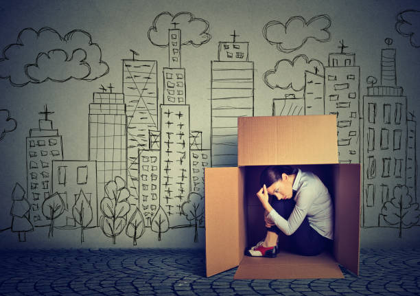 young woman hiding in the box on skyscraper city background - uneven stock photos and pictures