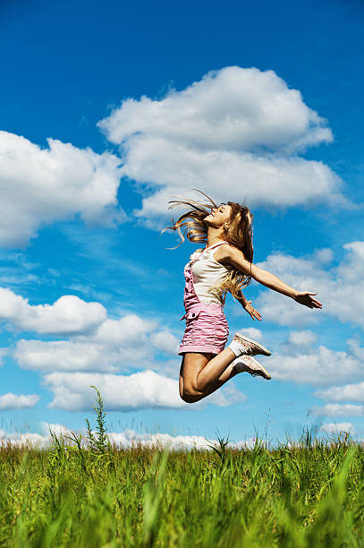 young woman high jumps stock photo