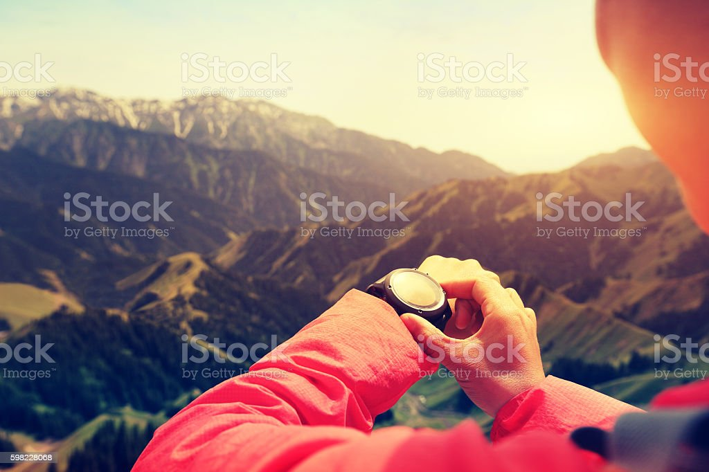 young woman hiker checking the altimeter on sports watch stock photo